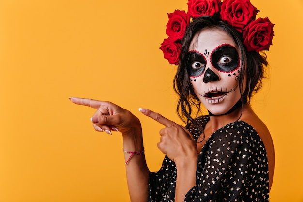 Modello femminile abbronzato in abito di halloween in posa con la bocca aperta. splendida ragazza in abiti tradizionali messicani che celebra il giorno dei morti.