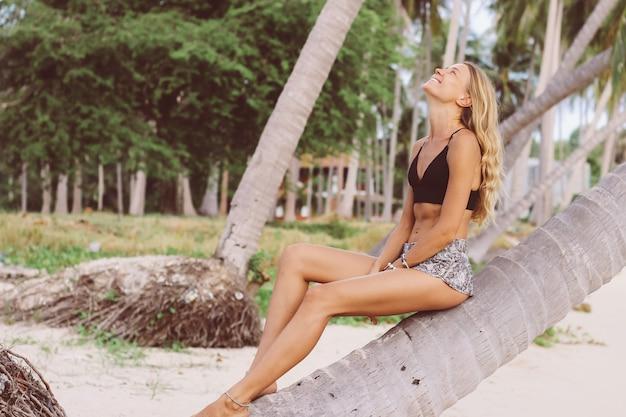 熱帯のビーチのヤシの木に日焼けしたフィットスリム白人モデル