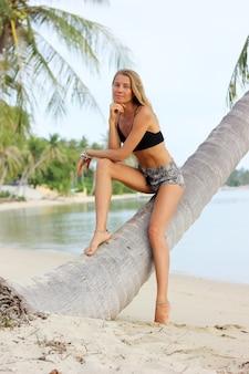 열 대 해변에서 야자수에 검게 맞는 슬림 백인 모델