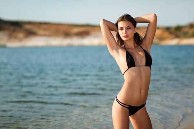 Tanned girl in black swimsuit posing on seashore