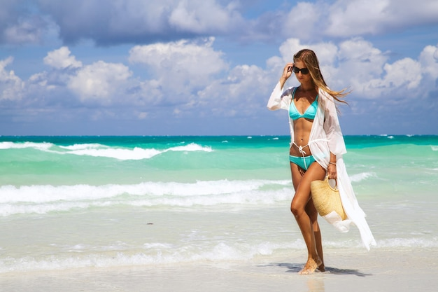 Tanned girl in blue bikini and white tunica holding fashionable straw bag and walking on the seashore.