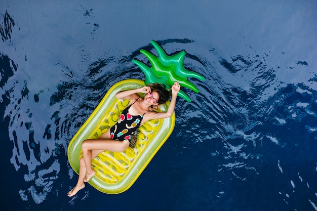 Tanned girl in funny swimsuit chilling at sea resort. overhead portrait of laughing pretty female model lying on mattress.