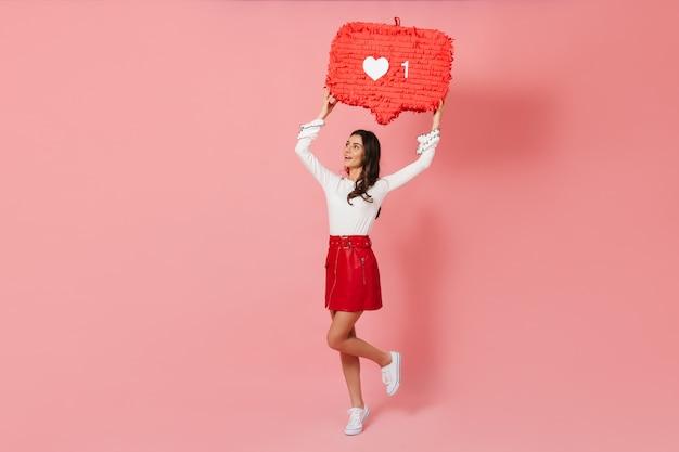 Загорелая девушка в модной кожаной юбке подпрыгивает на розовом фоне с декором в виде лайков из instragram.