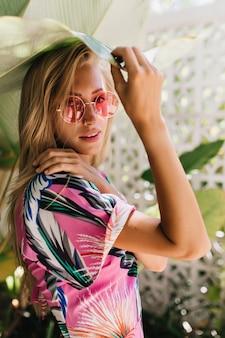 식물을 만지고 유행 분홍색 안경에 무두 질된 소녀.