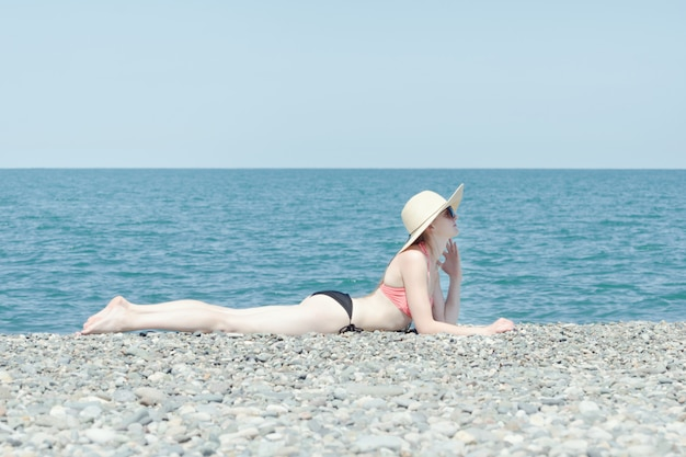 Not a tanned girl lies on the beach with a hat and sunbathes.