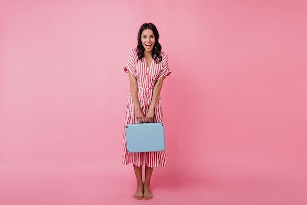 Загорелая девушка удивленно смотрит, скромно демонстрируя свой яркий портфель. изображение европейской модели в летнем платье.