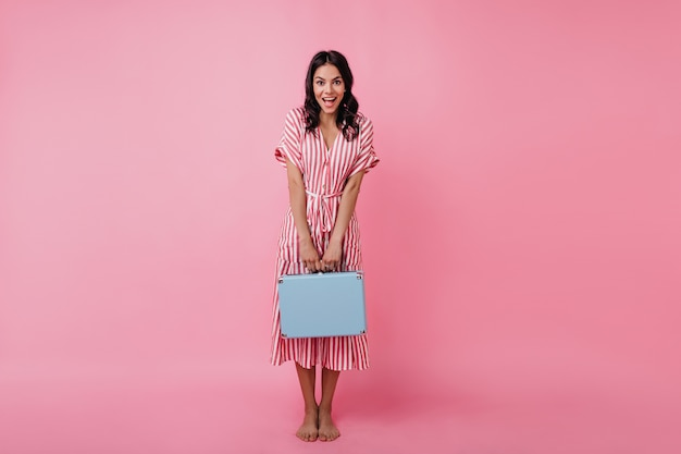 Tanned girl looks in surprise, modestly showing off her bright briefcase. picture of european model in summer dress.
