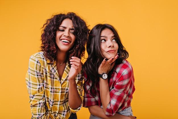 日焼けした女の子は、友達が冗談を言って笑っている間、ずる賢く見上げます。市松模様のシャツを着たポジティブな感情的な女の子の肖像画。