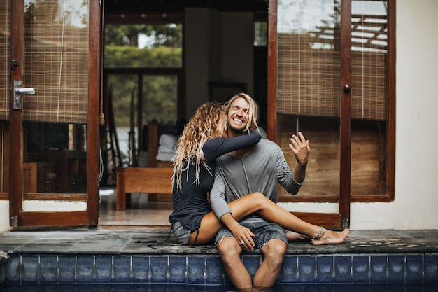 Tanned girl in shorts is hugging her laughing guy. couple sitting near pool
