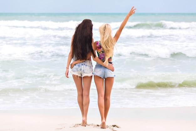 Загорелые девушки с длинными ногами стоят у океана и наслаждаются прекрасным видом на природу. портрет в полный рост босоногих дам в джинсовых шортах, проводящих утро в море.