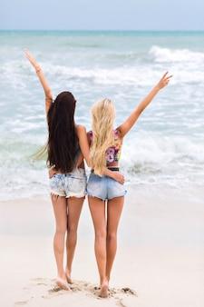 海の近くに立って、素晴らしい自然の景色を楽しんでいる長い脚を持つ日焼けした女の子。海で朝を過ごすデニムショートパンツで裸足の女性の屋外の全身肖像画。