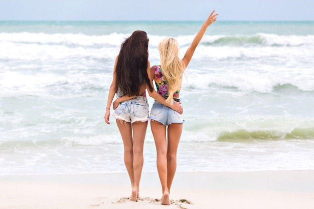 Tanned girls with long legs standing near ocean and enjoying amazing nature view. full-length outdoor portrait of barefooted ladies in denim shorts spending morning at sea.