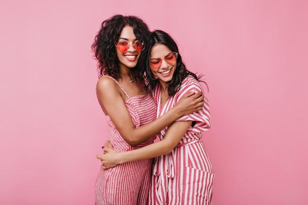 Le ragazze abbronzate con sorrisi bianchi sinceri si rallegrano dei servizi fotografici. fidanzate in tuta estiva in posa.