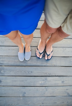 Tanned guy and girl are standing on a wooden bridge