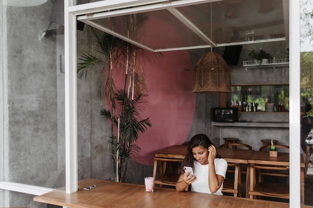 검게 그을린 여성은 목재 가구가있는 카페에 앉아 전화로 비디오를보고 있습니다.
