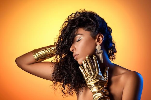 金色の背景に巨大なイヤリングで、金色の手袋でポーズをとる日焼けした豪華な女性。
