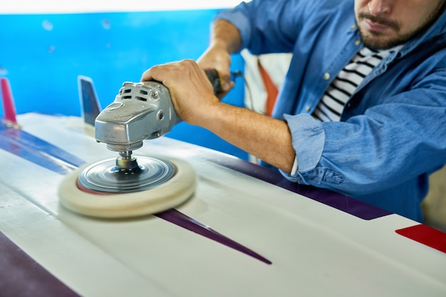 Tanned man polishing surfing board in workshop