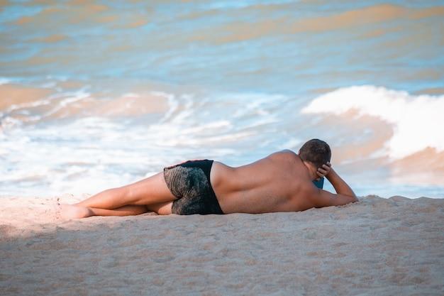 Загорелый мужчина с телефоном отдыхает на берегу морского пляжа. концепция путешествий и отдыха.