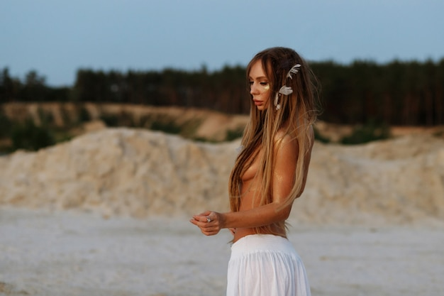 Tanned model in a white skirt with dreadlocks and feathers in her hair topless in the summer evening