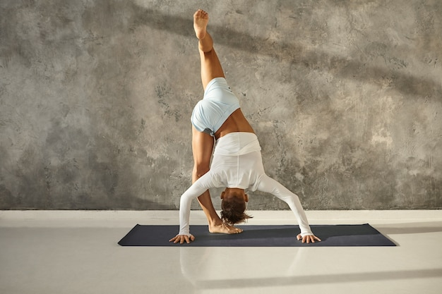 Tanned muscular guy doing urdhva prasarita eka padasana on mat. athletic man standing in balancing inversion posture, stretching and strengthening legs. yoga, concentration and coordination