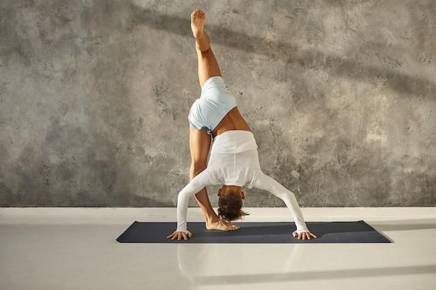 マットの上でurdhvaprasarita ekapadasanaをやっている日焼けした筋肉の男。反転姿勢のバランスを取り、脚を伸ばして強化する運動選手。ヨガ、集中力、協調性