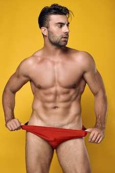 Tanned muscular man wearing a red underwear on yellow