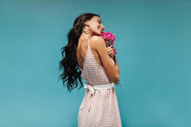 Ragazza abbronzata positiva con capelli ondulati lunghi scuri in orecchini e vestiti moderni rosa e bianchi a quadri che sorride sul muro
