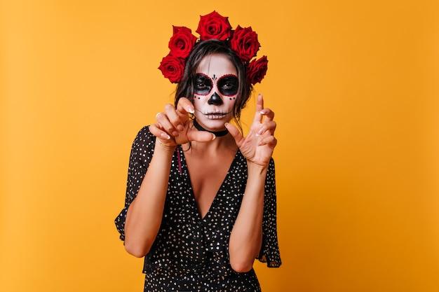 할로윈 메이크업 서 밝은 배경에 검게 예쁜 여자. 죽은 자의 날을 축하하는 머리카락에 꽃이있는 멋진 여성 좀비.