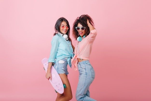 Загорелая серьезная азиатская девушка в розовых очках стоит с африканским кудрявым другом и держит скейтборд. стильная спортивная женщина-мулатка в джинсах с наушниками играет с волосами