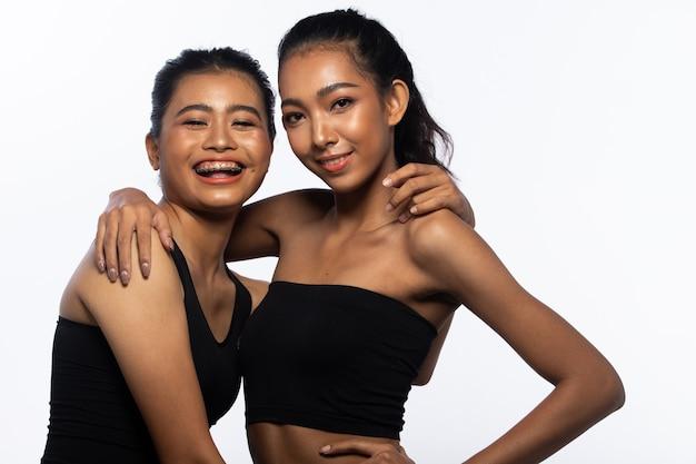 日焼けした肌の女性は長い黒髪がカメラを見て笑顔を表現しています。アジアの女の子の肖像画は白い壁、コピースペースに黒いドレスを着ています