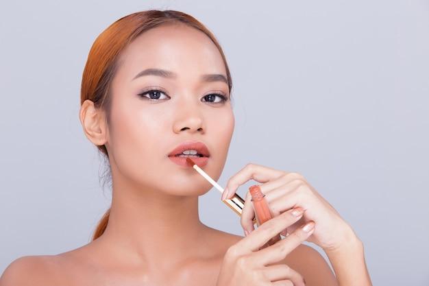 Загорелая кожа молодая модная азиатская модель женщины представляет, демонстрируя косметический макияж, упаковку продуктов, пустую копию пространства на ее ладони, поворот сбоку, вид сзади, открытое плечо, топлес, студийное освещение, реклама