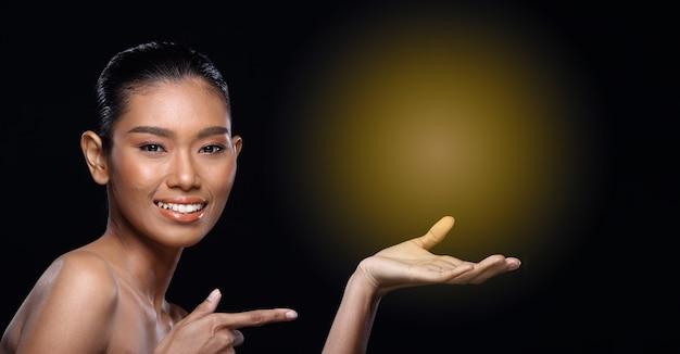 Загорелая кожа молодая мода азиатская женщина модель представляет продукты пустую копию пространства на ее ладони руки, повернуть вид сзади сбоку открытое плечо топлес, студийное освещение черный фон рекламная зона