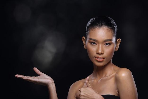 日焼けした肌の若いファッションアジアの女性モデルのプレゼント彼女の手のひらの上に製品の空のコピースペースを示し、側面の背面図を開いて肩をトップレス、スタジオ照明の黒い背景の広告エリア