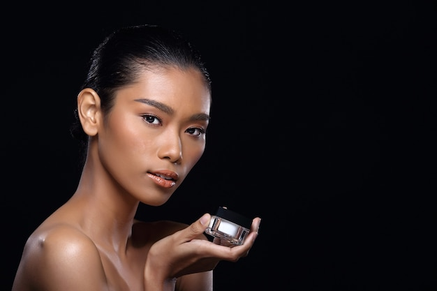Загорелая кожа молодая модная азиатская женщина-модель присутствует, демонстрируя косметический пакет с копией пространства под рукой, ладонь, поворот сбоку, вид сзади, плечо, топлес, студийное освещение, черный фон, рекламная зона