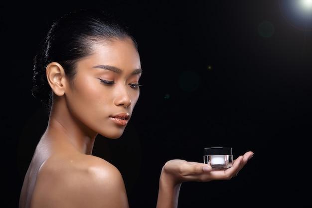 日焼けした肌の若いファッションアジアの女性モデルのプレゼント手手のひらに製品治療パッケージのコピースペース、トップレスのサイドリアビューショルダー、スタジオ照明黒の背景広告エリアを表示