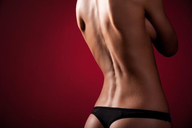 Загорелая, стройная женщина топлес и в черных стрингах позирует, повернувшись назад