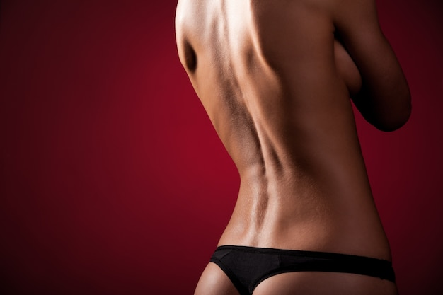 Tanned, slim woman topless and in black thong posing turning back