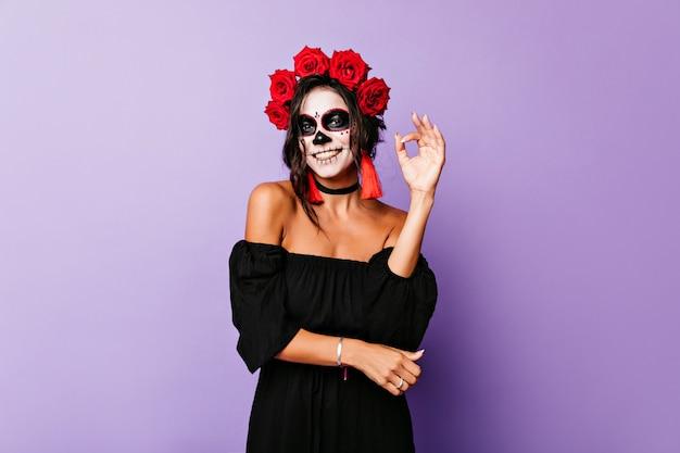 Ragazza sorridente abbronzata con capelli neri agghiacciante sulla parete viola. giovane donna allegra in costume mascherato che gode del servizio fotografico.
