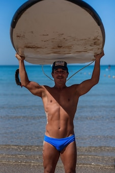 Tanned sporty man holds his surfboard over his head on the sea.