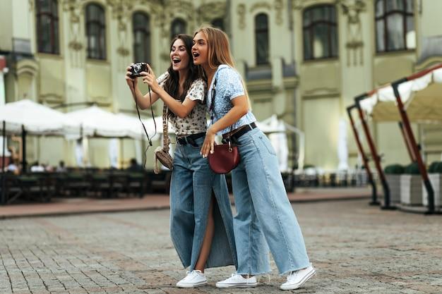 デニムのスタイリッシュなパンツと花柄のブラウスで日焼けした驚きの興奮した女性はショックを受けたように見え、レトロなカメラを持っています