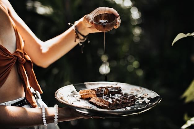 La donna abbronzata in reggiseno marrone tiene la ciotola con lo sciroppo d'acero e posa in giardino