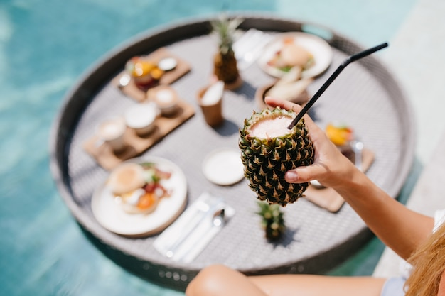 Tanned woman holding sweet pineapple cocktail. female model posing during lunch in pool.