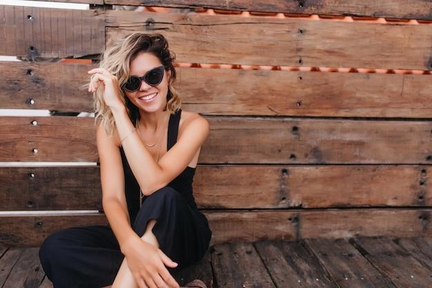 Загорелая женщина в солнечных очках сидит со скрещенными ногами. великолепная барышня в черном наряде позирует на деревянной стене.