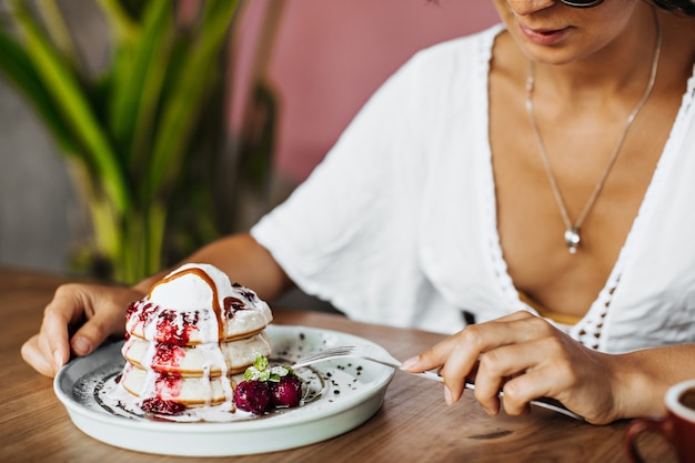 白いティーの日焼けした女性はフォークを保持し、おいしいデザートを食べる