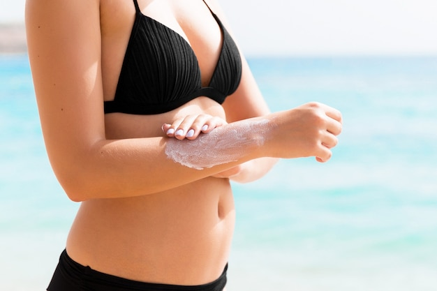 Tanned woman is applying sunscreen on her hand at the beach