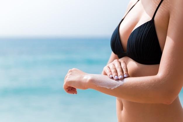 검게 그을린 여자는 해변에서 그녀의 손에 자외선 차단제를 적용하고 있습니다.