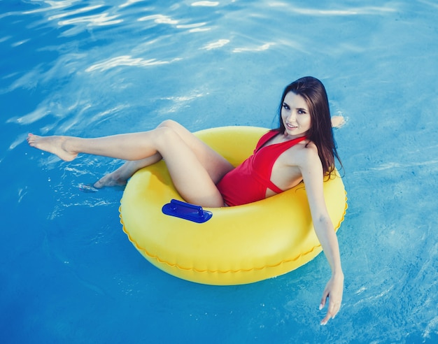 Tanned woman lies on an inflatable yellow circle