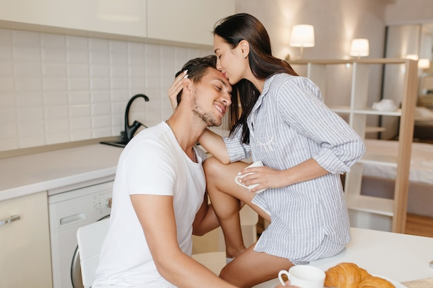 Tanned woman in male shirt sitting on table and kissing husband in forehead