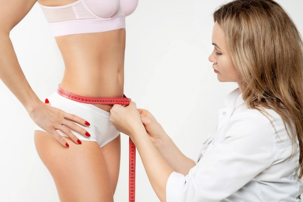 Tanned woman measuring hips with measuring tape