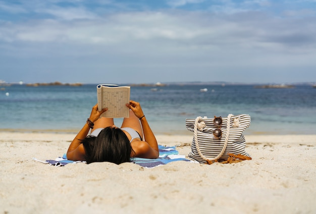 Tanned woman reading and enjoying on beach by the ocean